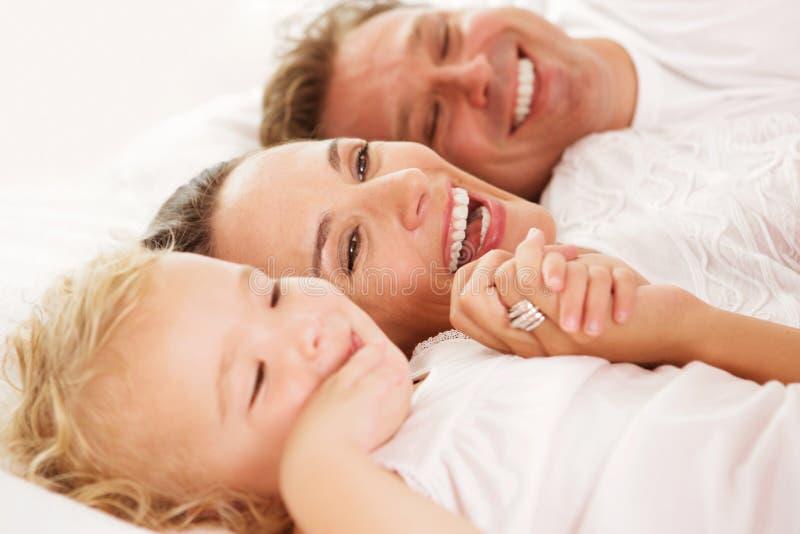 Menina bonito com seus pais que encontram-se na cama fotos de stock royalty free