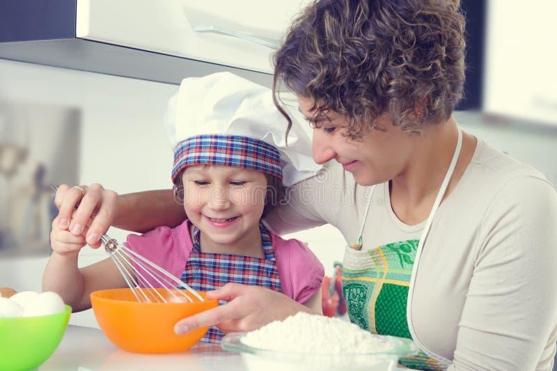 A menina bonito com sua mãe coze cookies em casa fotografia de stock