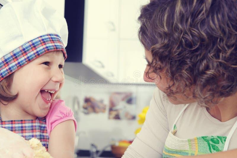 A menina bonito com sua mãe coze cookies em casa foto de stock