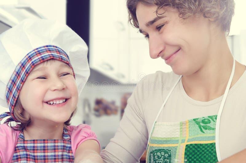 A menina bonito com sua mãe coze cookies em casa imagens de stock royalty free