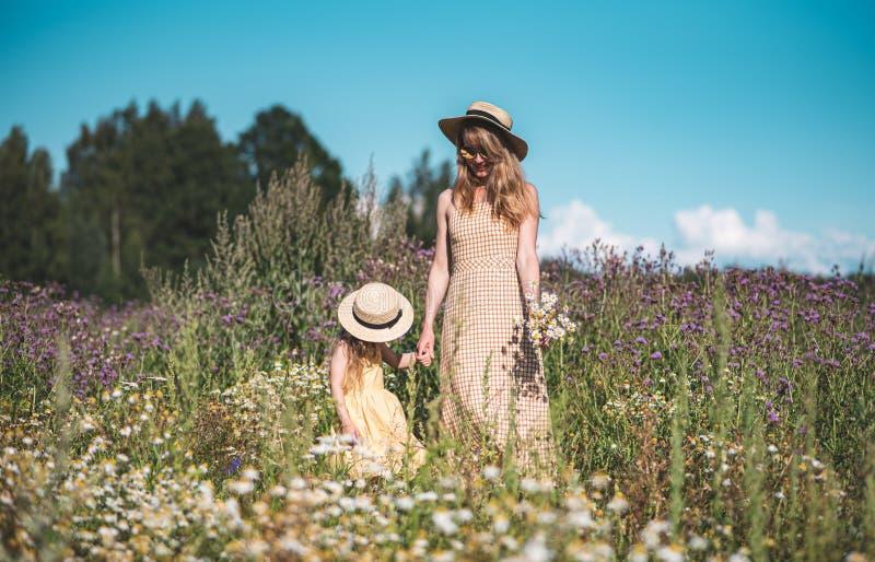 Menina bonito com sua mãe que anda no campo de flores fotografia de stock royalty free