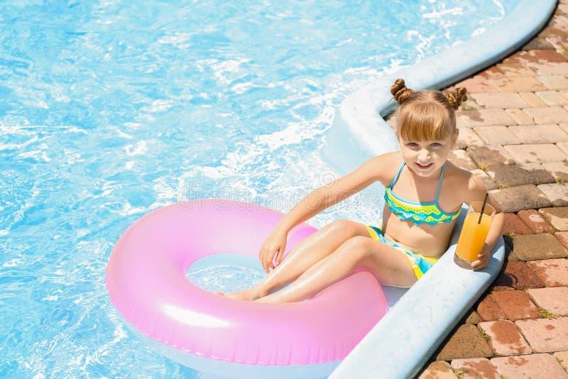 Menina bonito com suco bebendo do anel inflável na piscina imagem de stock royalty free