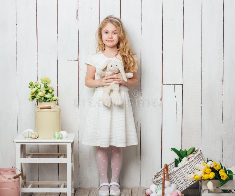 Menina bonito com um brinquedo do coelho de coelho no fundo de madeira branco imagem de stock royalty free
