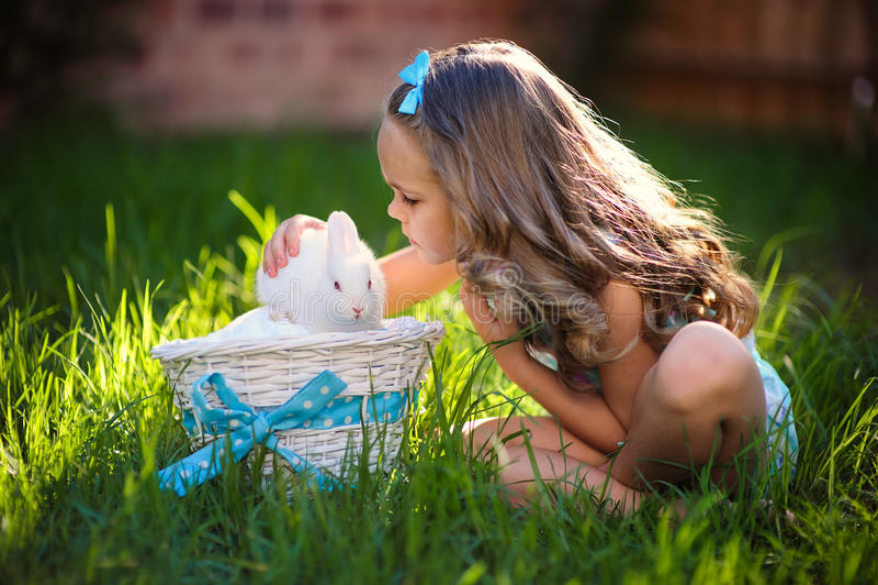 A menina bonito com um coelho de coelho tem um easter na grama verde fotos de stock royalty free