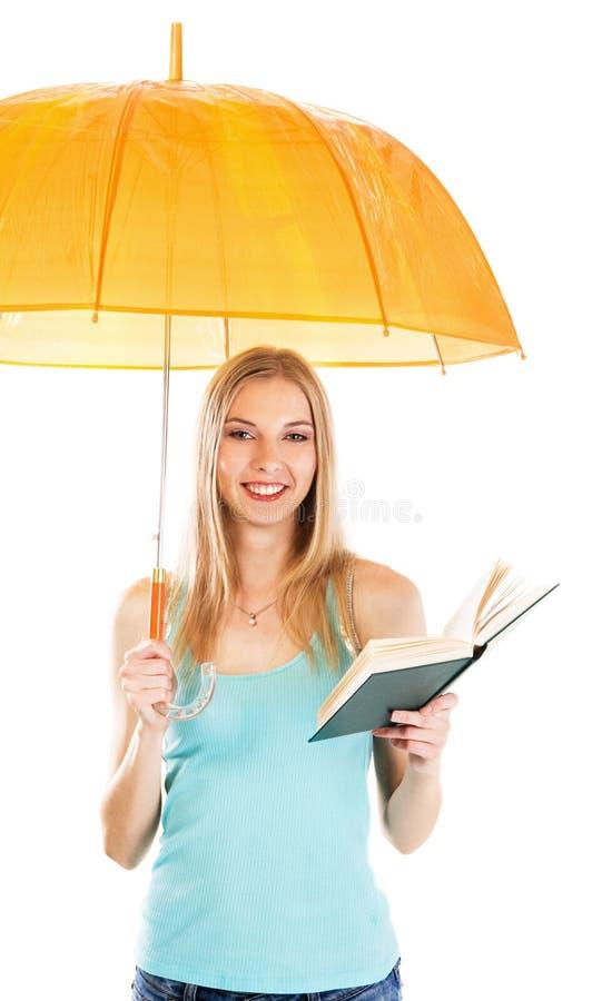 Menina bonito com um livro sob o guarda-chuva de encontro imagem de stock royalty free