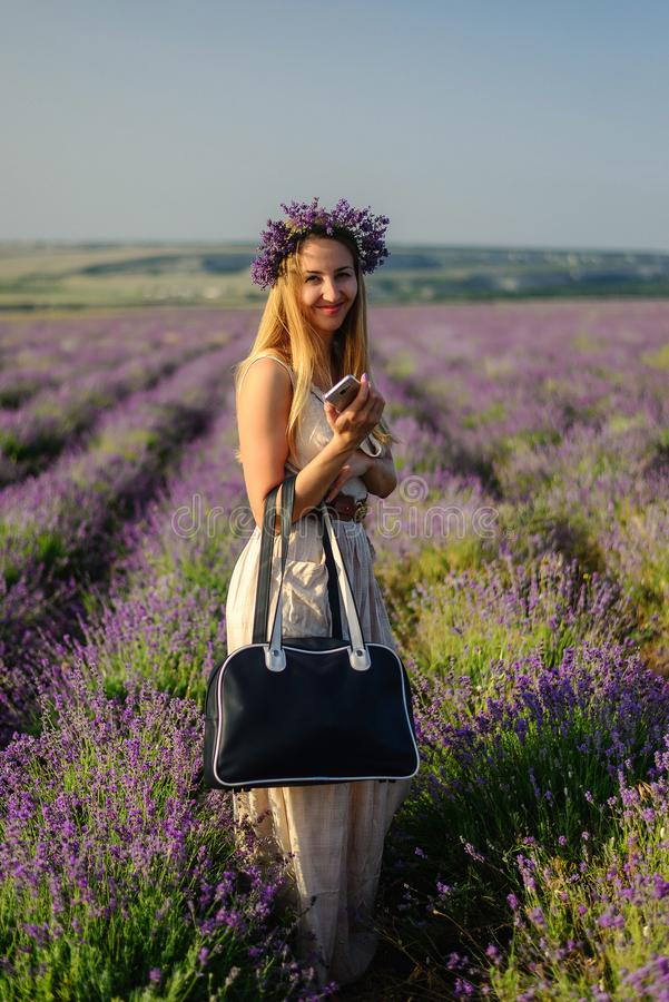 Menina bonito com uma grinalda da flor em sua cabeça e em uma mala de viagem nela imagem de stock royalty free