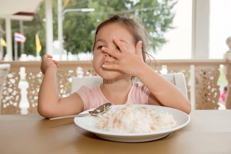 A menina bonito come o arroz em um café do verão imagem de stock royalty free