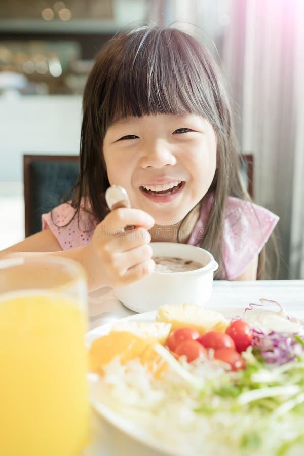 A menina bonito come o café da manhã imagem de stock