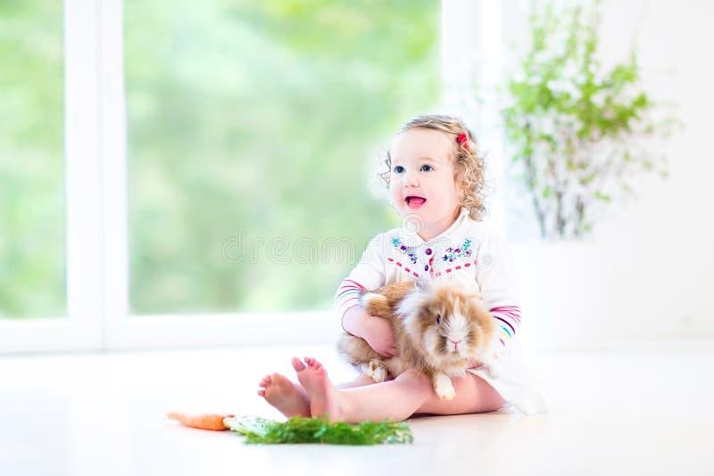 Menina bonito da criança com cabelo encaracolado com coelho real imagem de stock