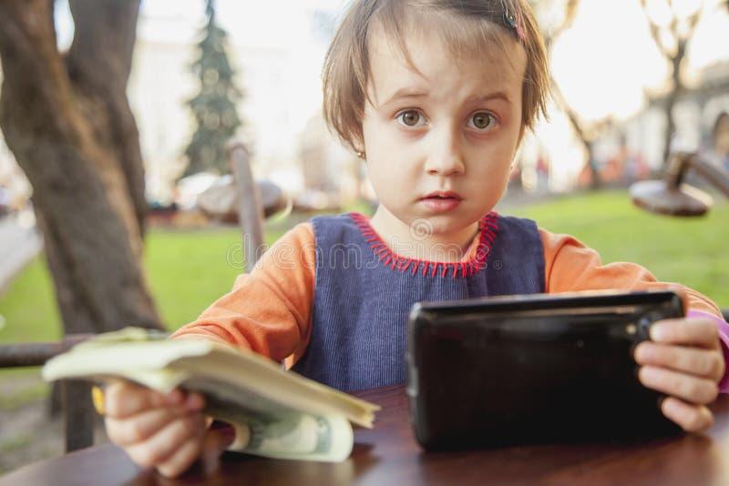 Menina bonito da criança com moedas como um símbolo da carteira móvel das moedas Conceito do neg?cio fotografia de stock royalty free
