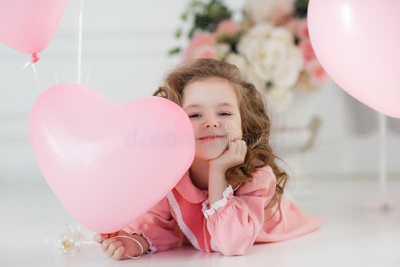 Menina bonito da criança de seis anos no vestido cor-de-rosa com os balões cor-de-rosa na forma do coração imagens de stock