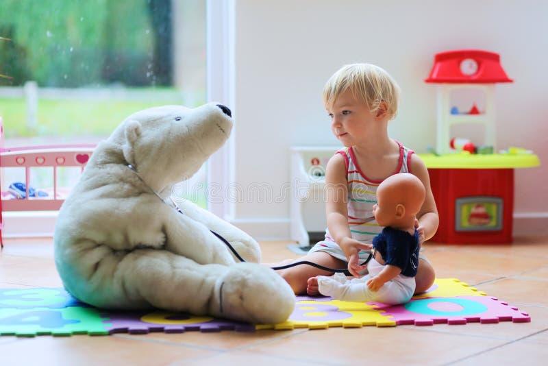 Menina bonito da criança em idade pré-escolar que joga o jogo do doutor com seus brinquedos imagem de stock royalty free