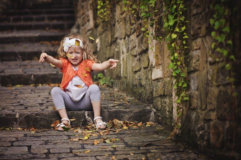 Menina bonito da criança nas folhas de jogo do casaco de lã alaranjado ao sentar-se na estrada de pedra imagem de stock