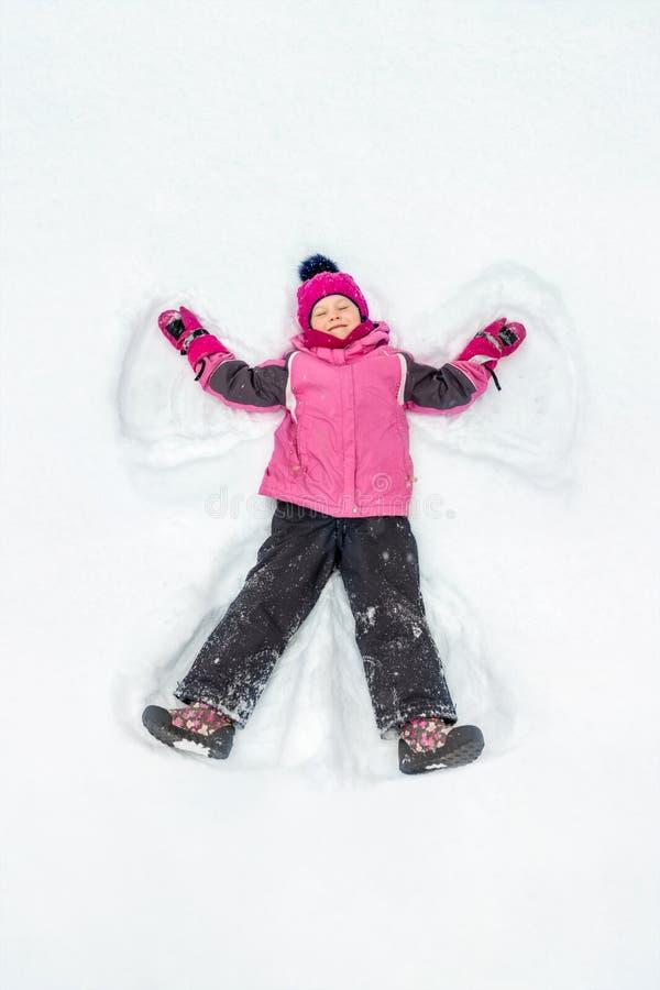 Menina bonito da criança no terno morno do esporte do esqui que faz o anjo da neve fora Caçoe ter o divertimento que encontra-se  imagem de stock royalty free