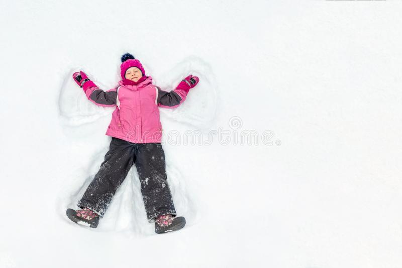 Menina bonito da criança no terno morno do esporte do esqui que faz o anjo da neve fora Caçoe ter o divertimento que encontra-se  fotos de stock