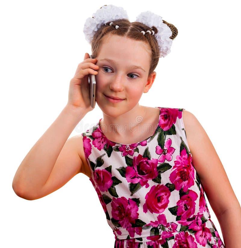 Menina bonito da criança no vestido colorido que guarda um smartphone fotografia de stock royalty free