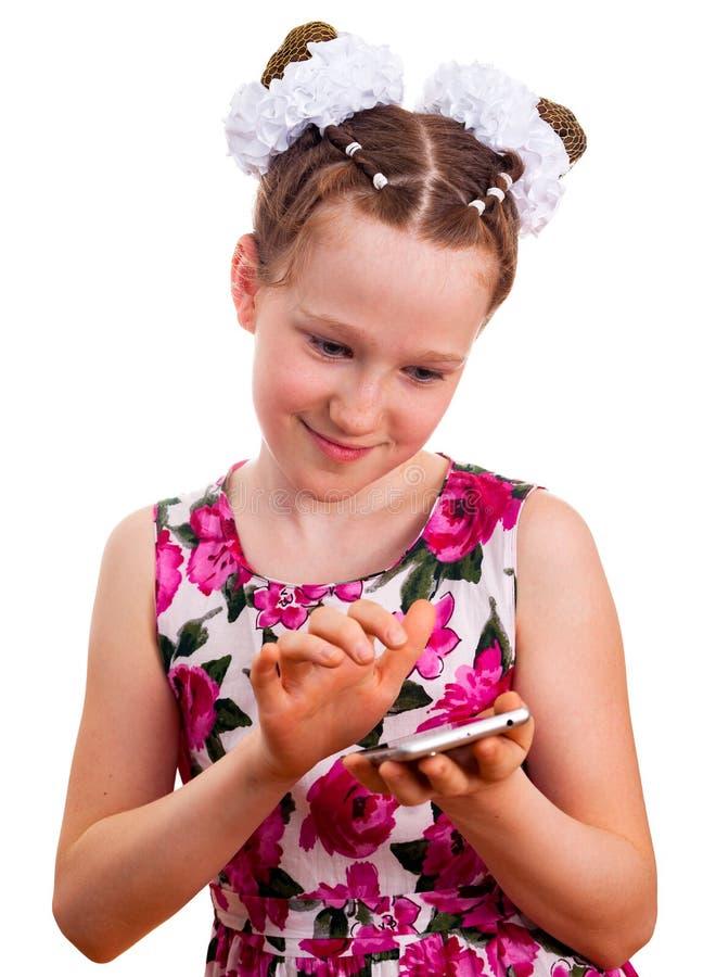 Menina bonito da criança no vestido colorido que guarda um smartphone imagem de stock