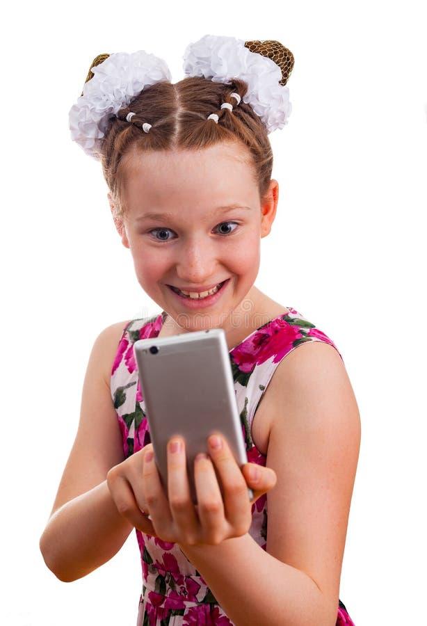 Menina bonito da criança no vestido colorido que guarda um smartphone foto de stock royalty free
