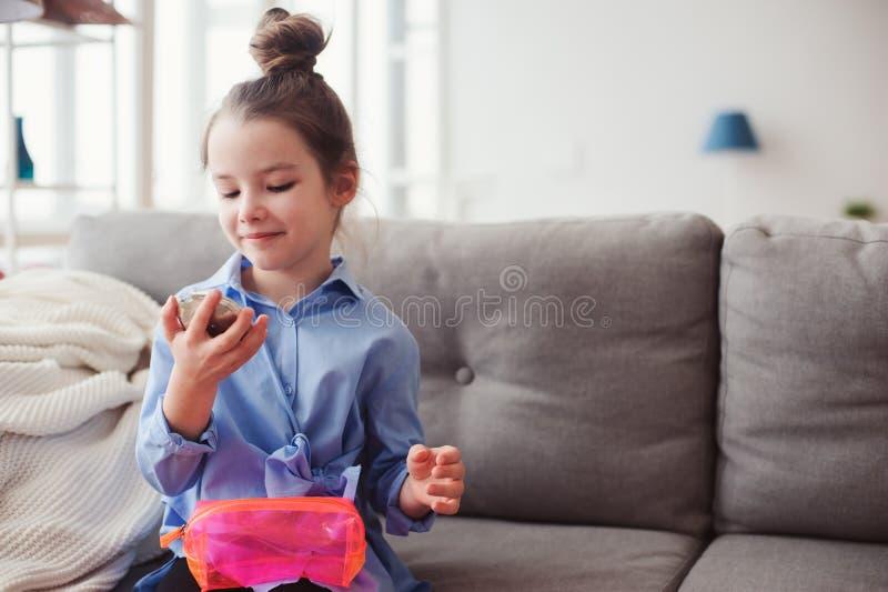 A menina bonito da criança pequena com espelho e o cosmético ensacam a verificação do penteado em casa imagens de stock