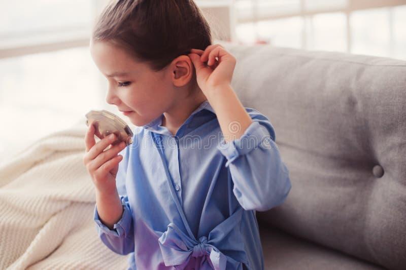 A menina bonito da criança pequena com espelho e o cosmético ensacam a verificação do penteado em casa foto de stock