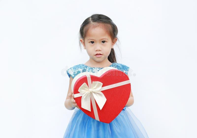 Menina bonito da criança pequena que mantém a caixa de presente vermelha do coração para o dia de Valentim isolada no fundo branc imagens de stock royalty free