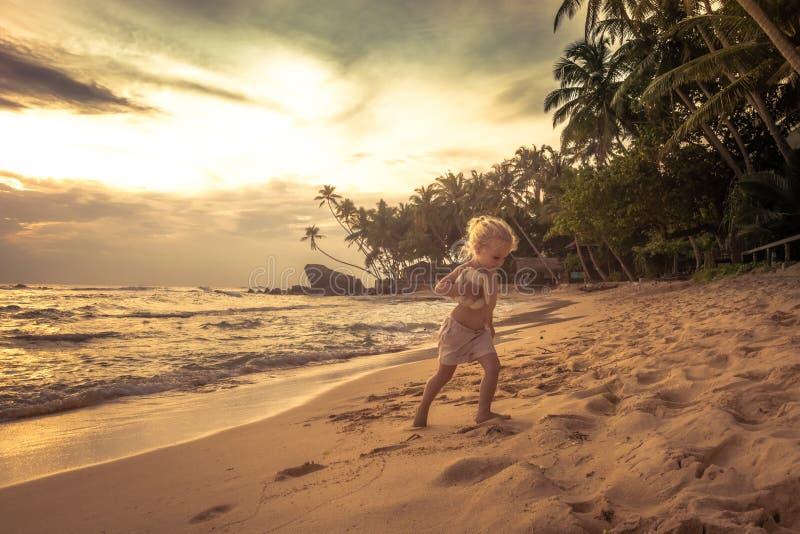 Menina bonito da criança da criança que anda na praia do por do sol durante o estilo de vida feliz do curso da infância do concei imagens de stock