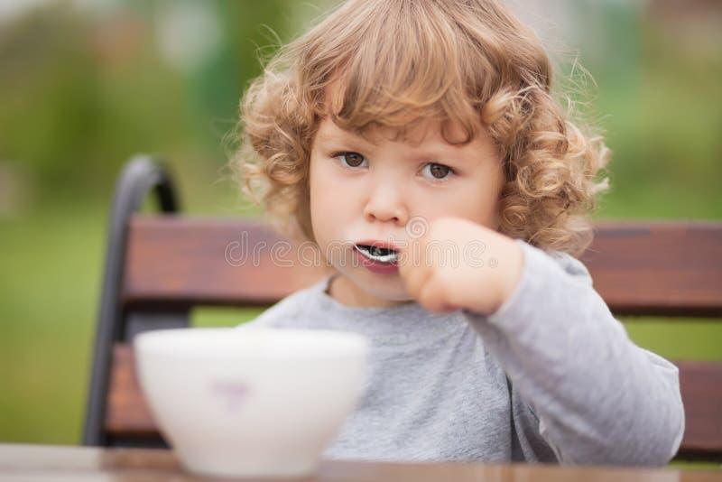 Menina bonito da criança que come o café da manhã fotos de stock