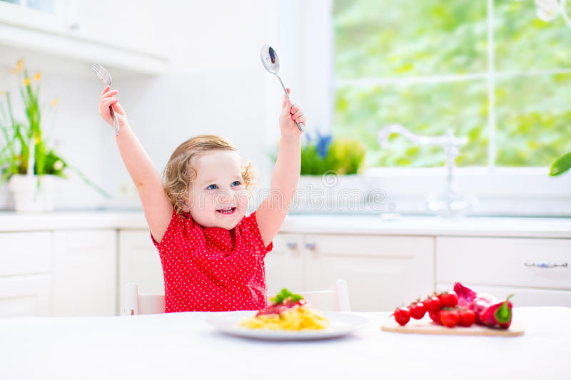 Menina bonito da criança que come os espaguetes em uma cozinha branca imagens de stock