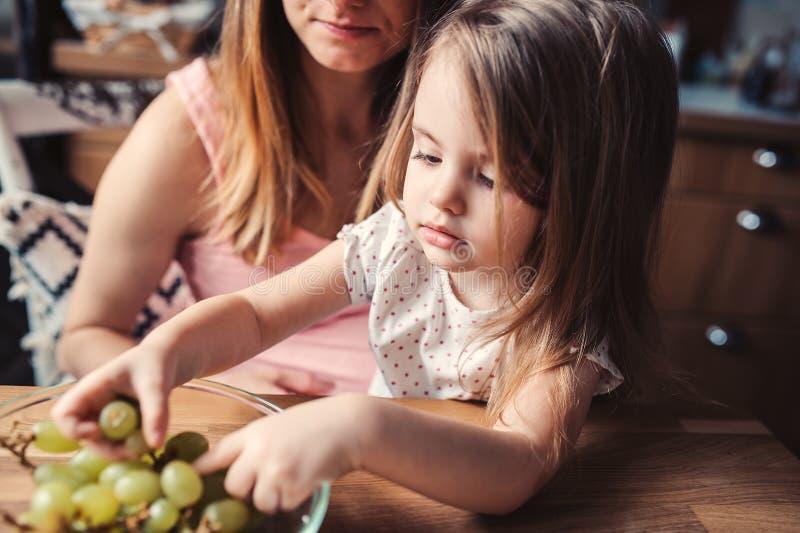 Menina bonito da criança que come uvas com a mãe na cozinha fotos de stock royalty free