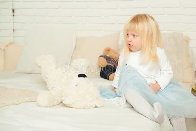 Menina bonito da criança que senta-se na cama com seus brinquedos macios em uma sala clara Conceito do feliz aniversario fotos de stock