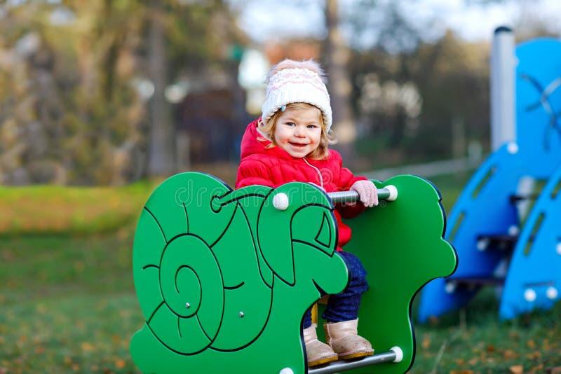 Menina bonito da criança que tem o divertimento no campo de jogos Criança pequena saudável feliz que escala, balançando e desliza imagens de stock royalty free