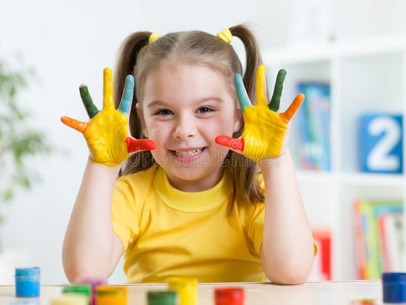 A menina bonito da criança tem o divertimento que pinta suas mãos imagem de stock royalty free