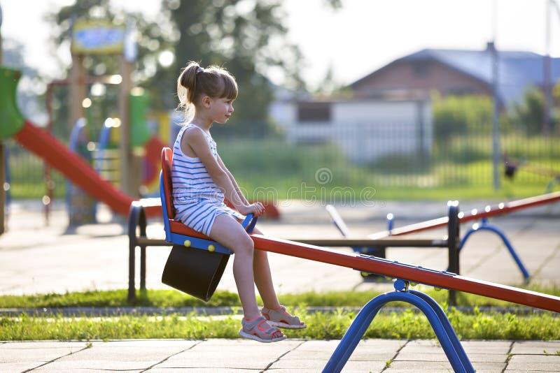 Menina bonito da jovem criança fora no balanço do balanço no dia de verão ensolarado imagem de stock