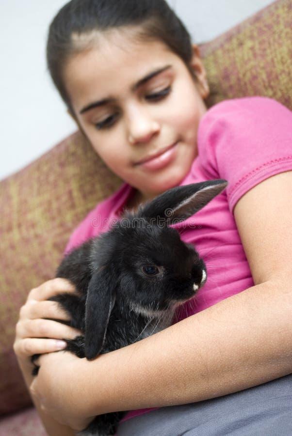 Menina bonito da raça misturada que guarda um coelho do animal de estimação foto de stock royalty free