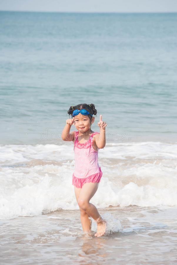 Menina bonito de Ásia que tem o divertimento na praia tropical ensolarada com wonde fotografia de stock royalty free