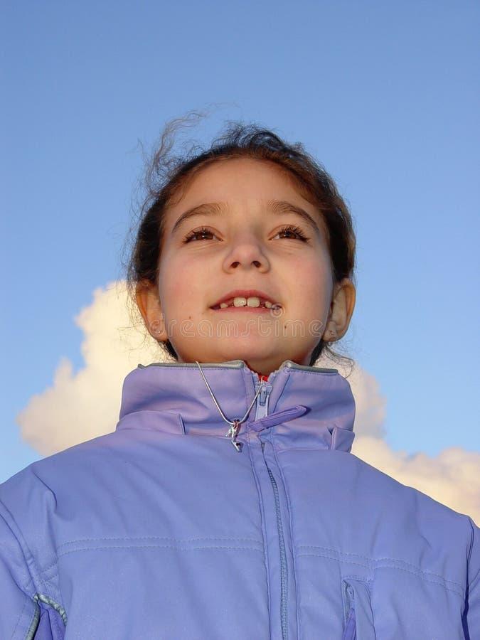 Menina bonito de encontro ao céu imagem de stock royalty free