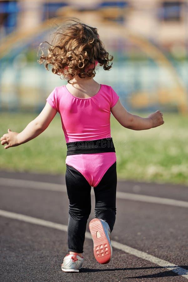 Menina bonito de Ittle que corre no estádio imagem de stock