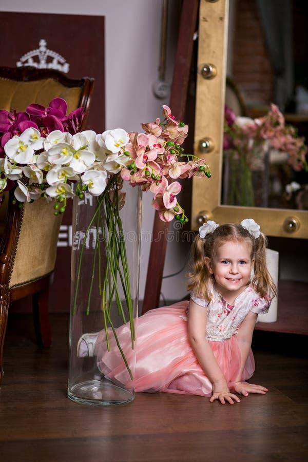 Menina bonito de olhos azuis em um vestido cor-de-rosa que senta-se perto de um vaso com orquídeas e sorriso fotografia de stock