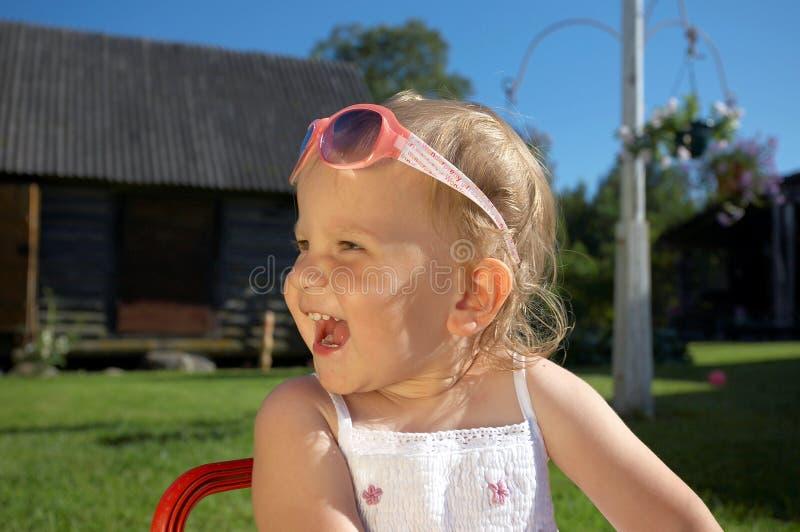 Menina bonito de riso com óculos de sol imagens de stock royalty free