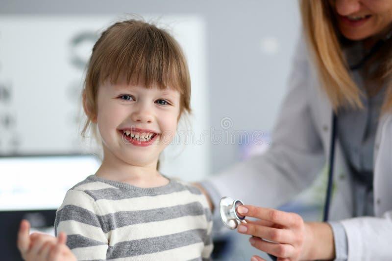 Menina bonito de sorriso com batimento card?aco de medi??o do doutor com estetosc?pio imagem de stock royalty free
