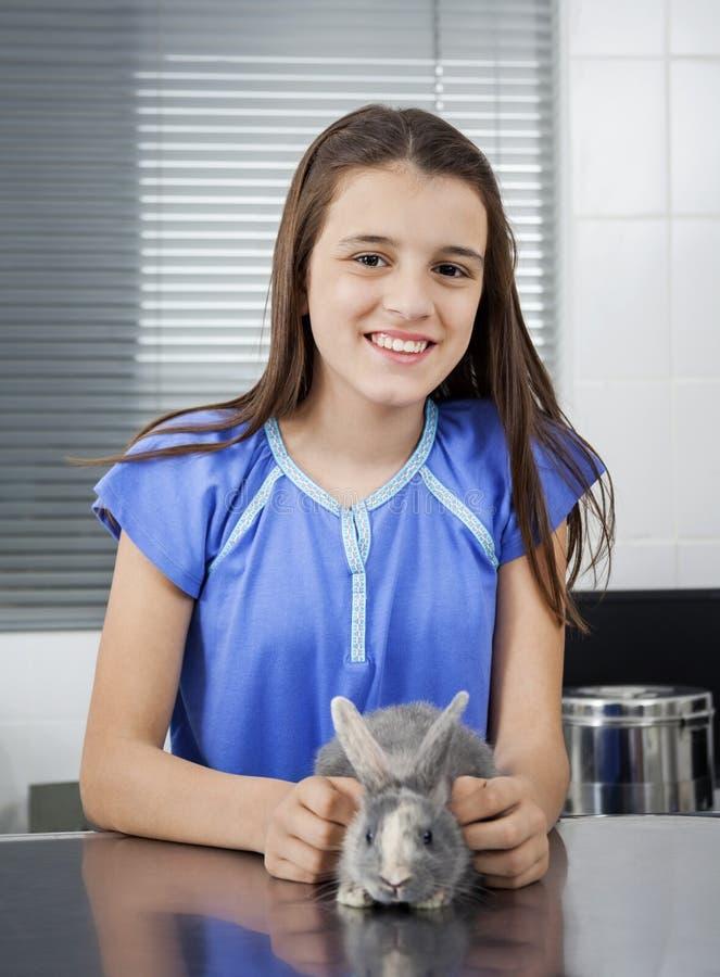 Menina bonito de sorriso com coelho na clínica foto de stock royalty free