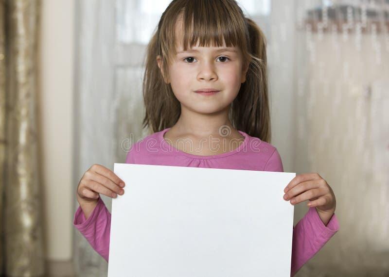 Menina bonito de sorriso feliz da crian?a que guarda a folha branca do espa?o da c?pia do papel de desenho Educa??o da arte, facu imagem de stock royalty free