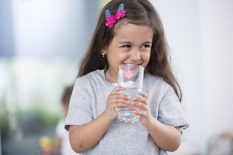 Menina bonito de sorriso que guarda o vidro da água em casa imagens de stock royalty free