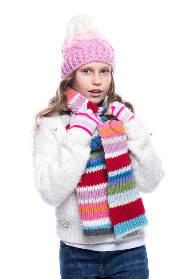 Menina bonito de sorriso que veste a camiseta feita malha e o lenço colorido, chapéu, mitenes isolados no fundo branco Roupa do i imagens de stock