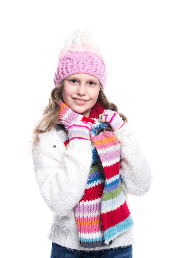 Menina bonito de sorriso que veste a camiseta feita malha e o lenço colorido, chapéu, mitenes isolados no fundo branco Roupa do i imagem de stock royalty free