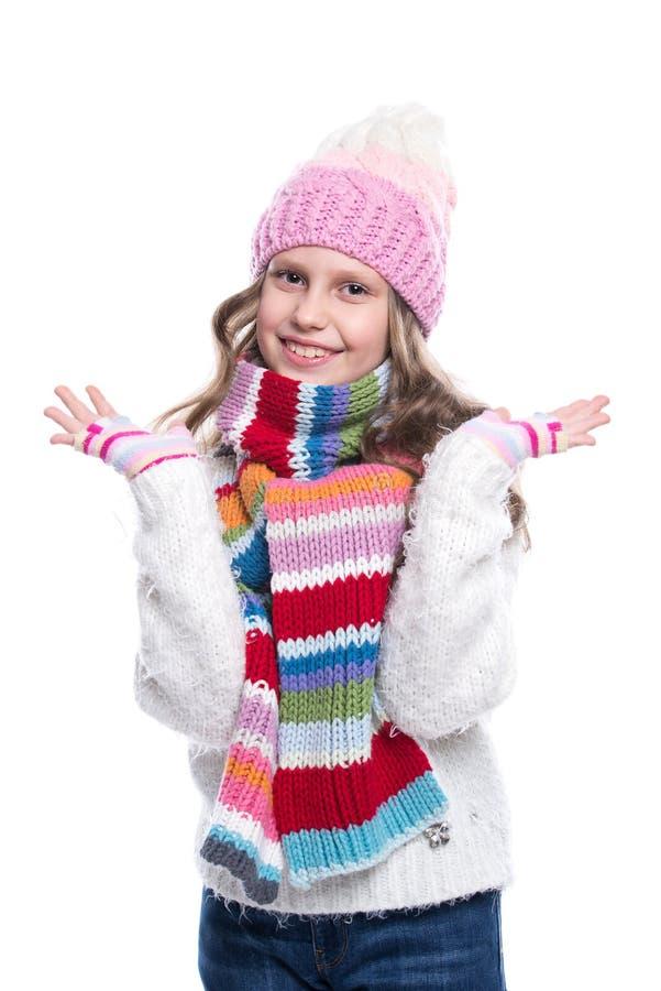 Menina bonito de sorriso que veste a camiseta feita malha e o lenço colorido, chapéu, mitenes isolados no fundo branco Roupa do i fotografia de stock