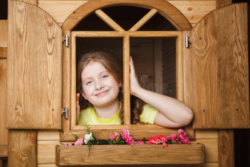 Menina bonito dentro da casa de madeira imagem de stock