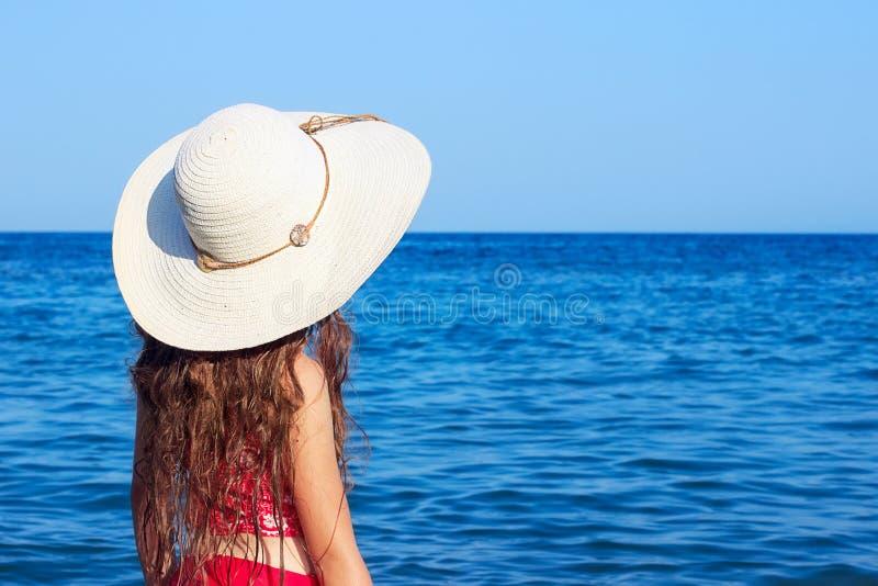 Menina bonito do adolescente que veste em um chapéu e em um roupa de banho grandes que olham imagem de stock