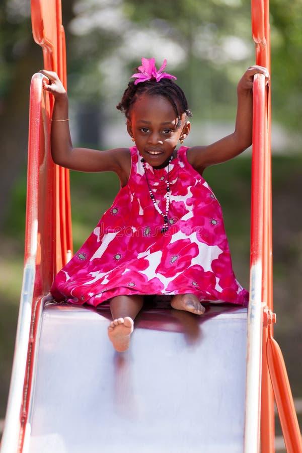 Menina bonito do americano africano no campo de jogos fotografia de stock royalty free