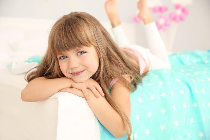 Menina bonito do aniversário que encontra-se na cama imagens de stock royalty free